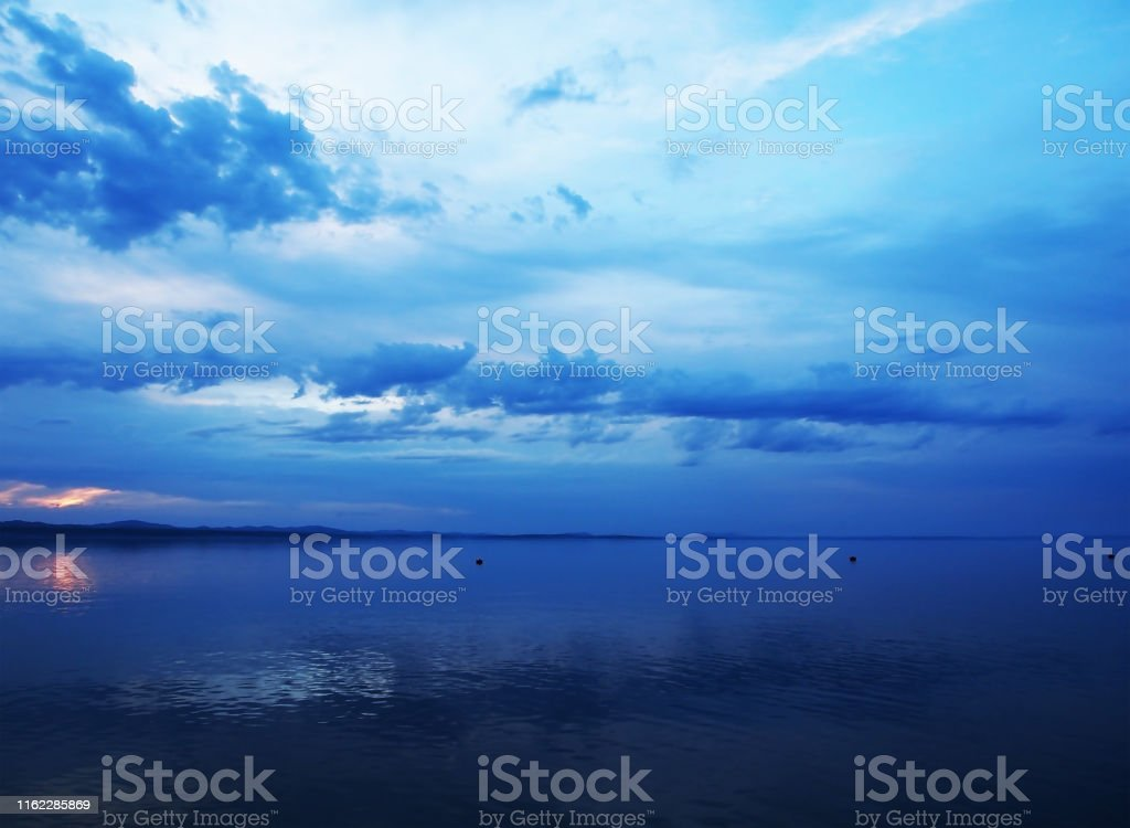 blue sunset sky over the lake with light smoky clouds over the...