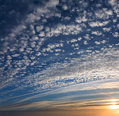 Summer evening sunset sky with fleece and spindrift clouds and sunshine background.