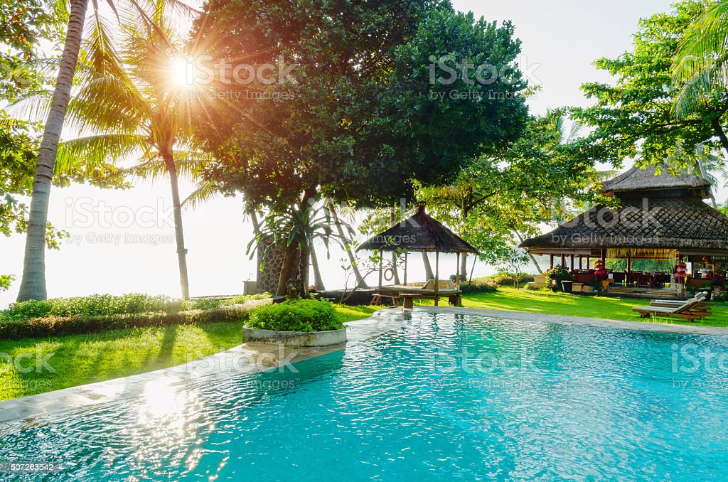 blue swimming pool under palms in Bali in sunlight stock photo