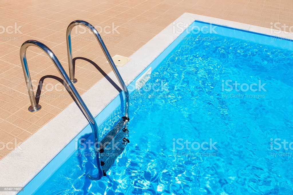 Blue swimming pool with ladder stock photo