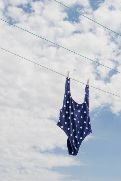 Blue swimsuit hanging in a clothes line with two clothespin against blue and cloudy sky. Hanging swimsuit against blue sky. stock photo