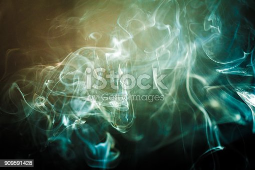 istock Blue swirling smoke abstract close up on black background 909591428