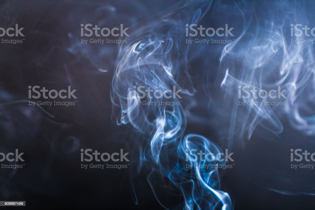 Blue swirling smoke abstract close up on black background stock photo