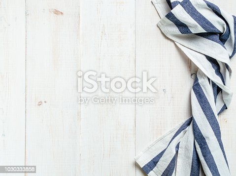 View from above on white wooden table with linen kitchen towel or textile napkin. Blue tablecloth on white wood tabletop. Copy space for text. Can use as mock up for design.