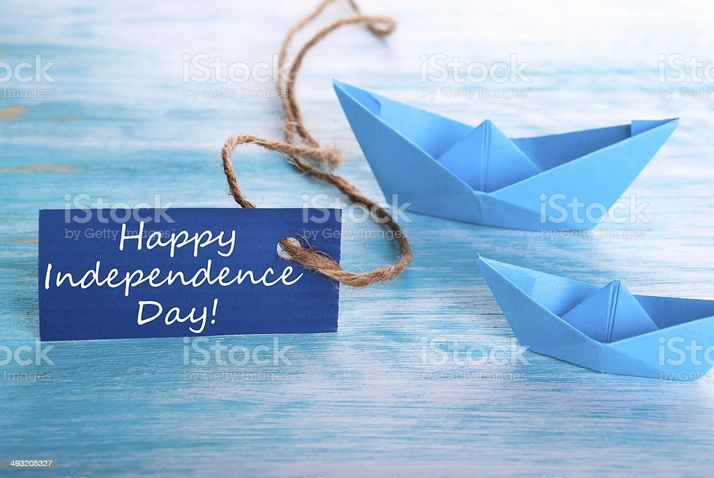 A Blue Tag with Happy Independence Day and Boats in the Background