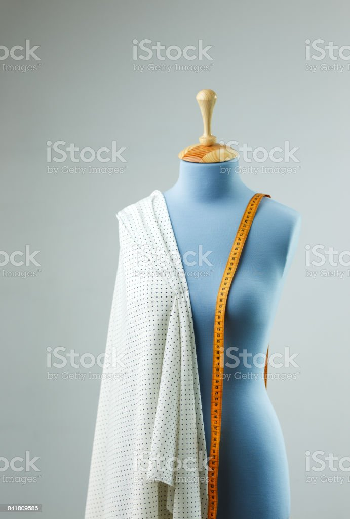 Blue tailor dummy with measuring tape alongside the wall. stock photo