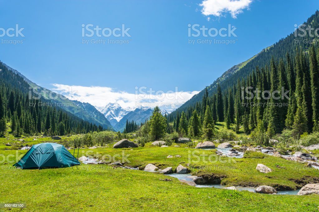 Blue tent on the banks of mountain rivers, Kyrgyzstan. стоковое фото