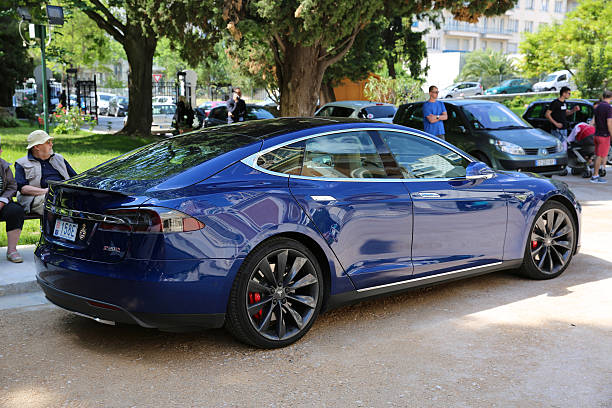 Blue Tesla Model S P90D - Side View Nice, France - May 15, 2016: Blue Tesla Model S P90D Car Parked in Front of the Nice Orthodox Church tesla model s stock pictures, royalty-free photos & images