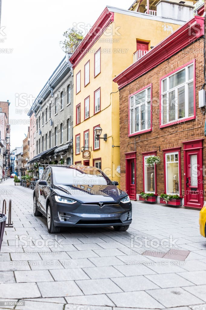 Blue Tesla Model X driving on cobblestone road in lower old town street called rue Sault-au-Matelot by restaurants, stores and souvenir shops stock photo