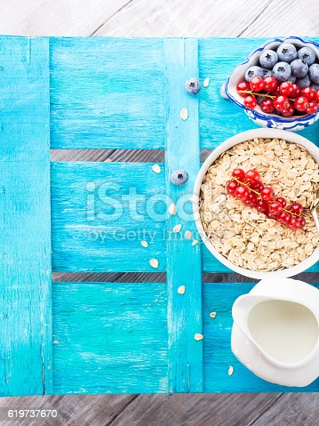 825171518 istock photo Blue textured background with rolled oats, berries and milk. Cop 619737670