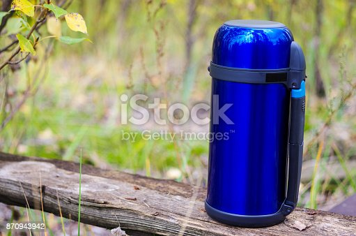 1135476970istockphoto A blue thermos for saving hot drinks. Thermos on the right. 870943942