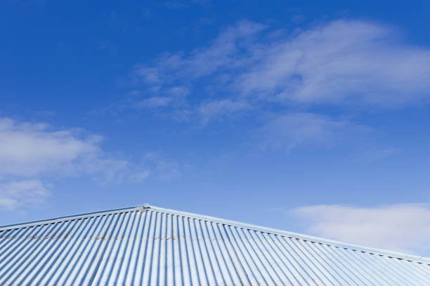 Blue tin corrugated tin roof with blue sky in the background stock photo