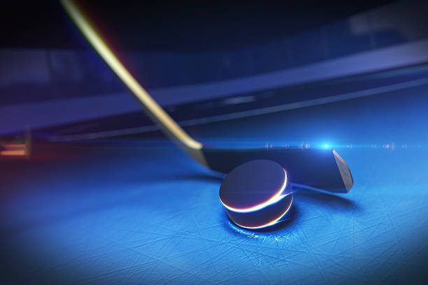 blue tinted close-up of a hockey stick and puck on ice rink - hockey puck stock photos and pictures