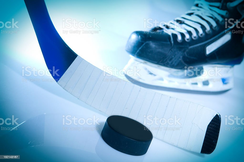 Blue tinted image of a hockey puck stick and ice skate stock photo