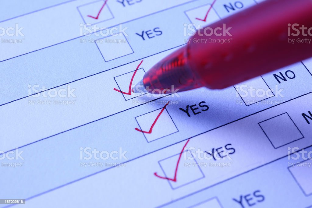 Blue tinted image of ball point pen marking a checkbox royalty-free stock photo