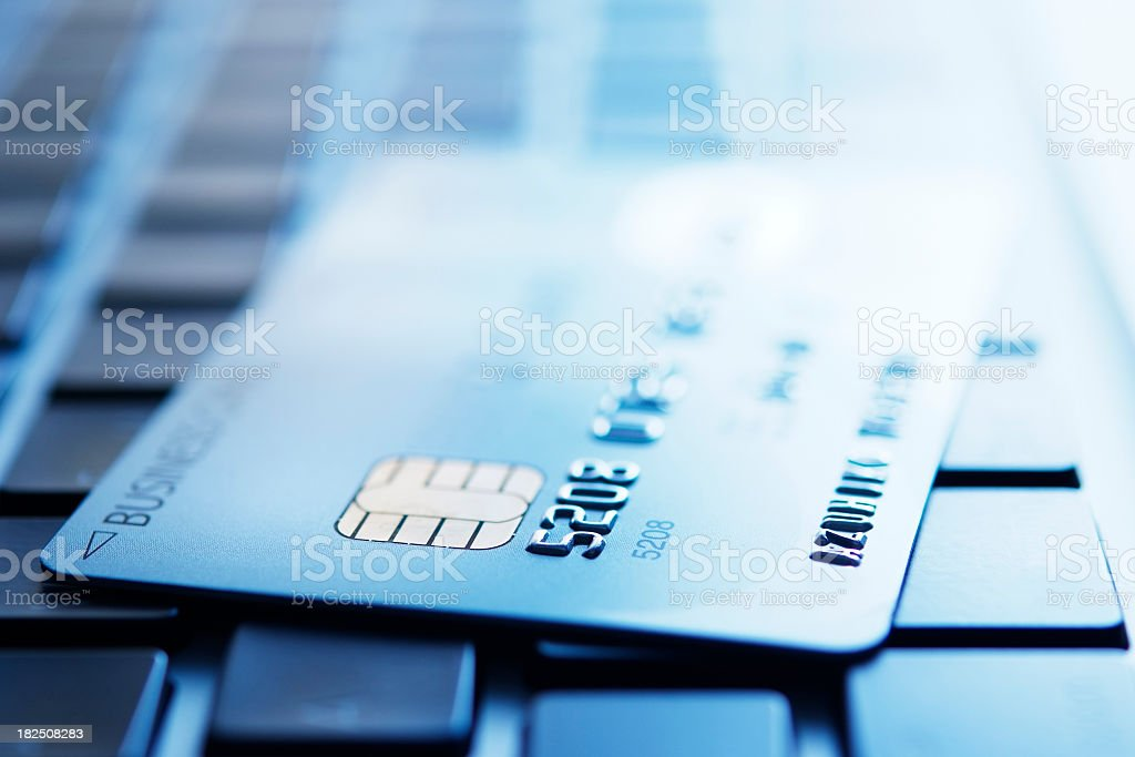 Blue tinted image of credit card on laptop royalty-free stock photo