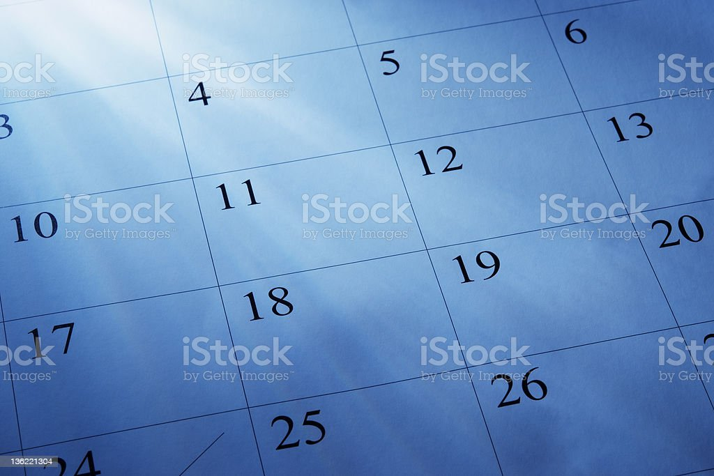 Blue tinted image of light rays and a calendars royalty-free stock photo