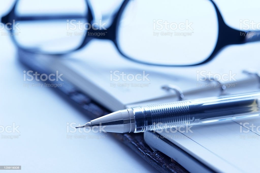 Blue tinted image of opened personal organizer with pen royalty-free stock photo