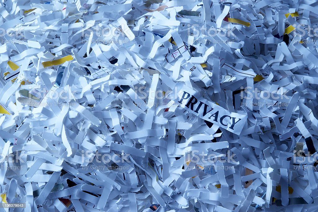 Blue tinted image of shredded privacy documents stock photo