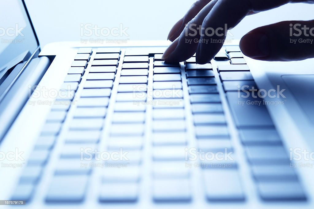 Blue tinted image of typing keyboard royalty-free stock photo
