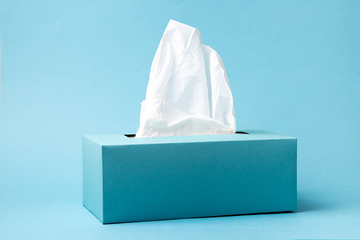 Light blue tissue box on blue background. Cold and flu concept. Minimal monochromatic composition.