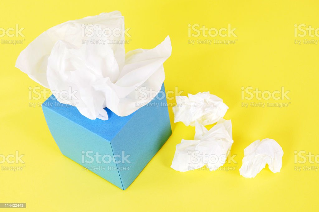 Blue tissue box with crumpled tissues beside it stock photo