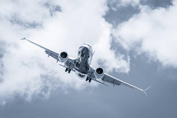 blue toned cross-wind passenger jet landing stock photo