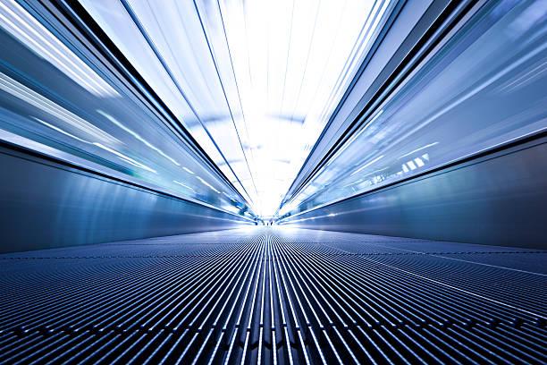 Blue toned low angle photo of moving walkway airport walkway connecting terminals. abstract tunnel, personal perspective. zoom effect stock pictures, royalty-free photos & images
