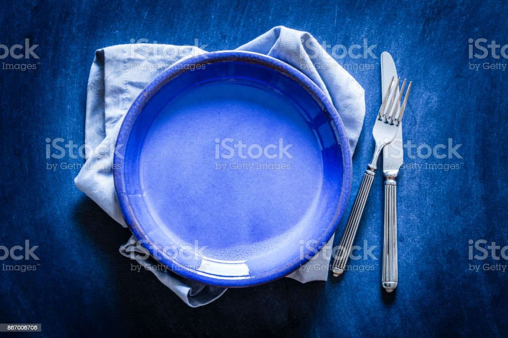 Blue toned place setting shot from above on dark background stock photo
