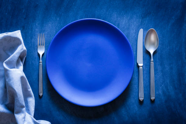 blue toned place setting shot from above on dark background - blue table setting stock photos and pictures