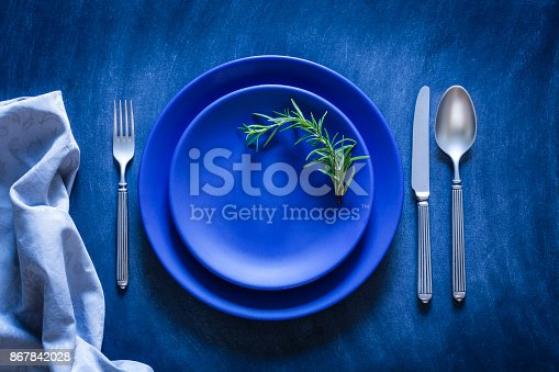 Top view of a blue plate with a spoon, fork and knife at each side shot against a textured bluish toned background. A gray textile napkin is at the bottom-left corner of an horizontal frame. A rosemary twig is on the plate. Predominant color is blue. Low key DSRL studio photo taken with Canon EOS 5D Mk II and Canon EF 100mm f/2.8L Macro IS USM