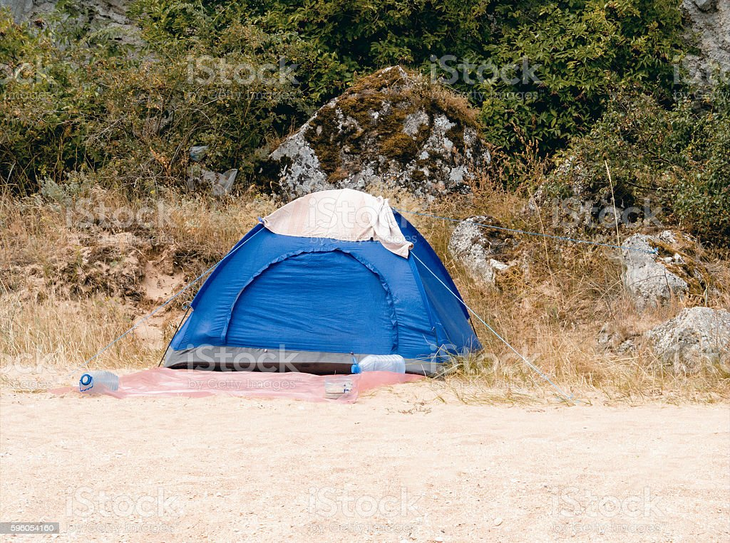 Blue tourist tent standing on the sandy beach royalty-free stock photo