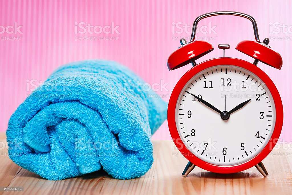 Blue towel and vintage clock on pink background. stock photo