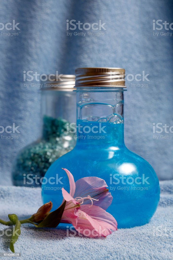 Blue towels and two bottles with shampoo and salt for baths royalty-free stock photo
