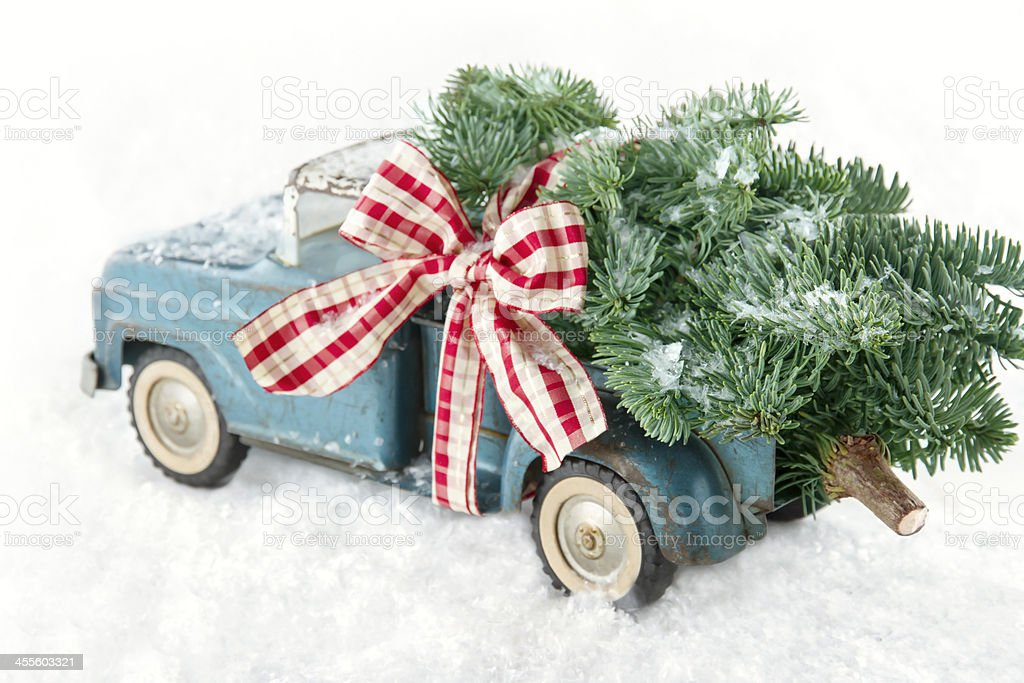 Blue toy truck carrying a Christmas tree Old blue toy truck carrying a green Christmas tree covered with snow and a red ribbon on white snowy bakcground Antique Stock Photo