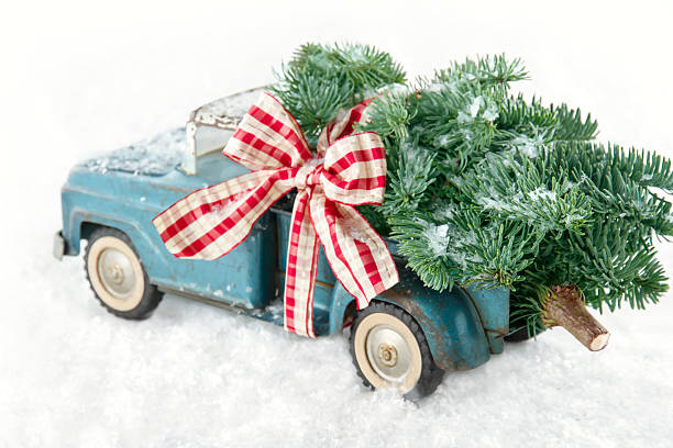Blue toy truck carrying a Christmas tree stock photo