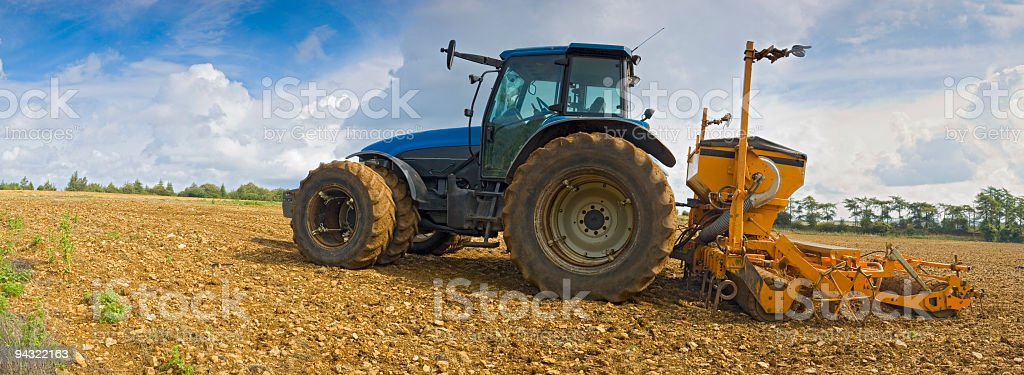 Blue tractor, brown soil stock photo