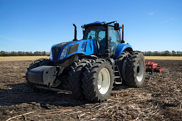 Blue tractor with plow stock photo