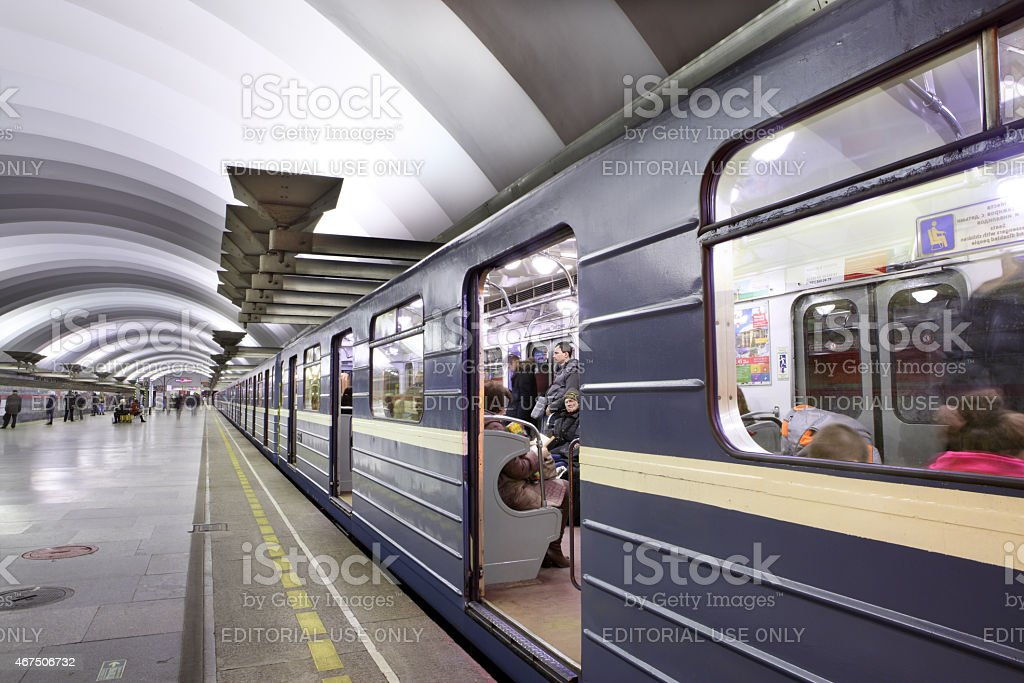 Blue train with passengers standing near platform to subway station stock photo