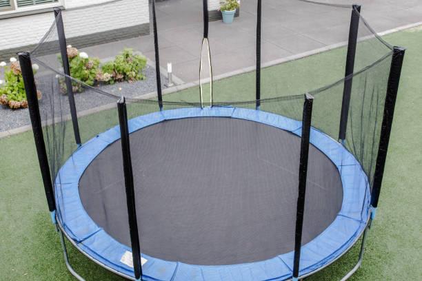 blaues trampolin mit sicherheitsnetz auf dem rasen im garten - gartentrampolin stock-fotos und bilder