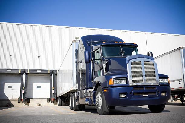 blue transport truck docking at warehouse - 裝貨 個照片及圖片檔
