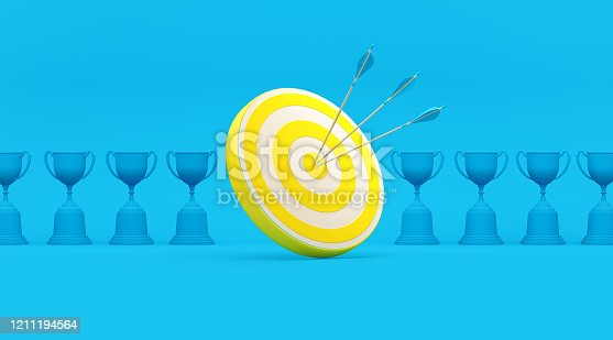istock Blue Trophies and Yellow Dart Target in a Row over Turquoise Background 1211194564