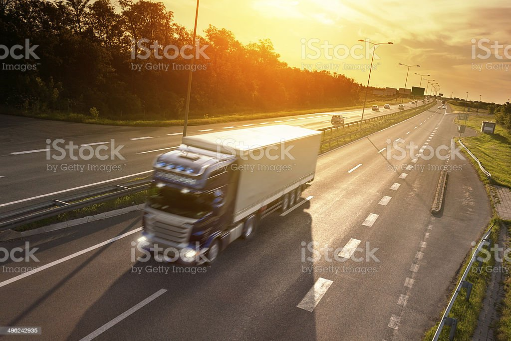 Blue truck in motion blur on the highway at sunset