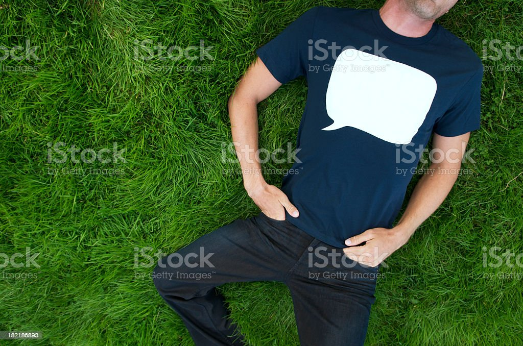 Blue T-Shirt Speech Bubble Man Lying Outdoors on Grass royalty-free stock photo