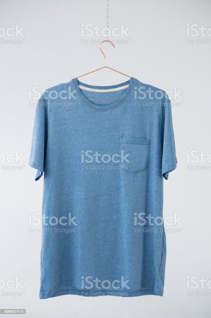 Blue t-shirt with pocket hanging on hanger stock photo