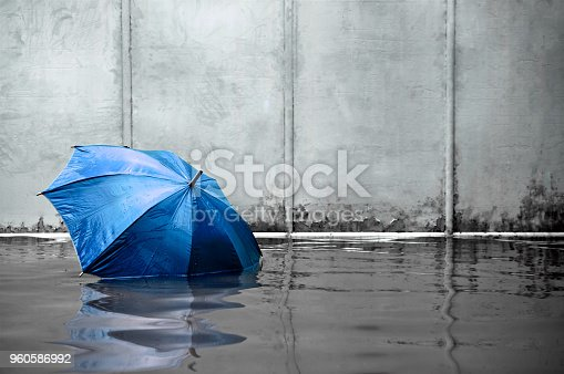 istock Blue umbrella floating concept. Flooded on street.  Waiting for help me after the rain. Black and white colors. Close up. 960586992