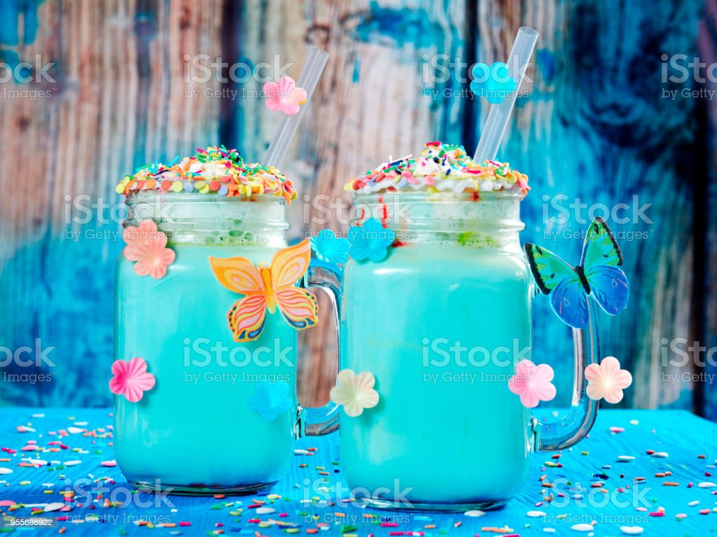 Blue unicorn hot chocolate with whipped cream, sugar and sprinkles set on a blue wooden board stock photo