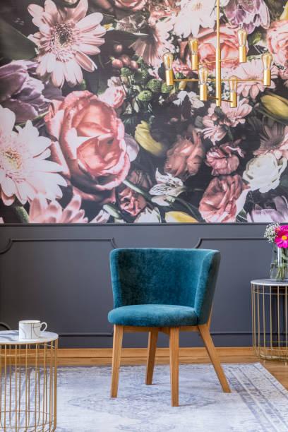 blauen polsterstuhl mit den hölzernen beinen auf einem grauen teppich in ein elegantes wohnzimmer interieur mit floral print tapete - blumendrucktapete stock-fotos und bilder