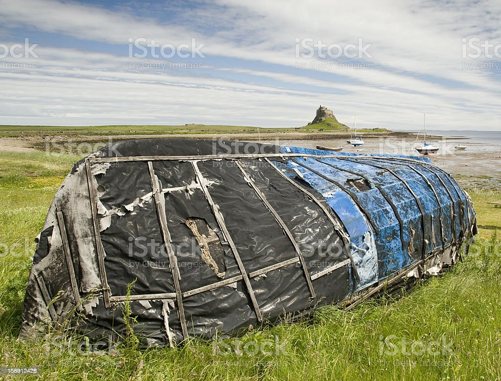 Blue upturned boat with Lindesfarne Castle royalty-free stock photo