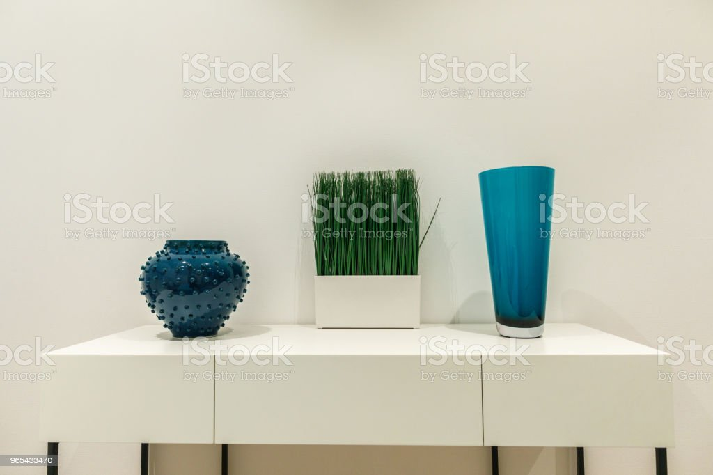 Blue vases and grass on white table by wall royalty-free stock photo